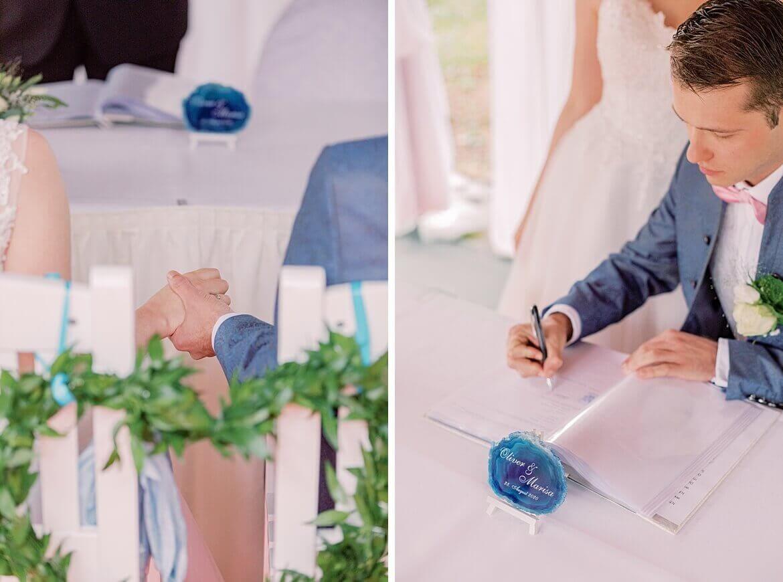 Brautpaar hält sich an Händen und unterschreibt Eheurkunde