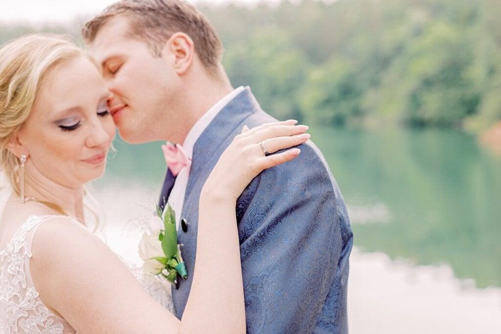 Brautpaar küsst sich vor See