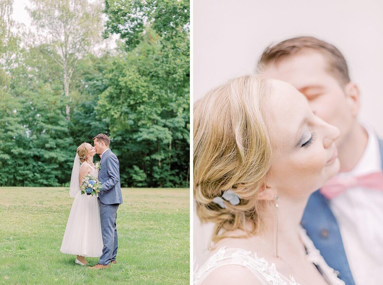 Brautpaar küsst sich auf Wiese