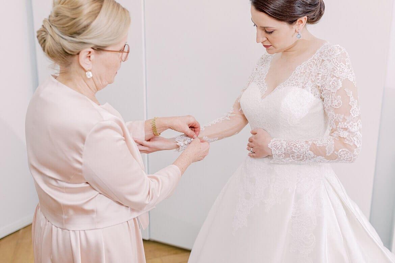 Brautmutter hilft Braut beim Anziehen des Brautkleids