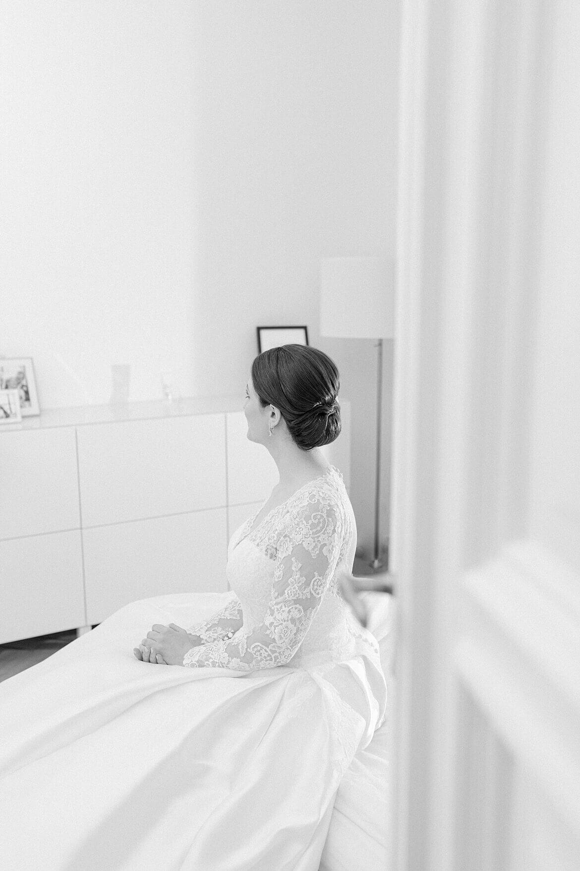 Braut sitzt auf Bett in Schwarz Weiß