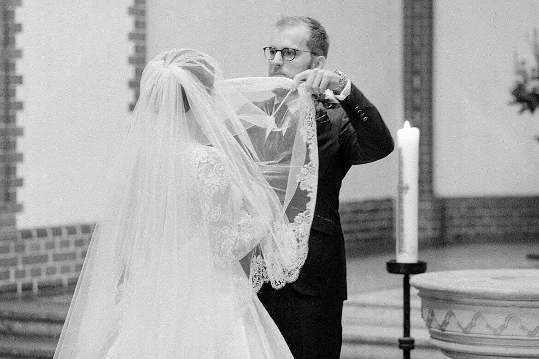 Bräutigam hebt Schleier in Schwarz Weiß