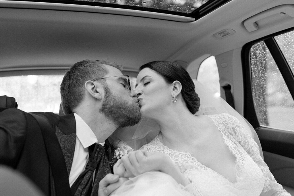Brautpaar küsst sich im Auto in schwarz weiß