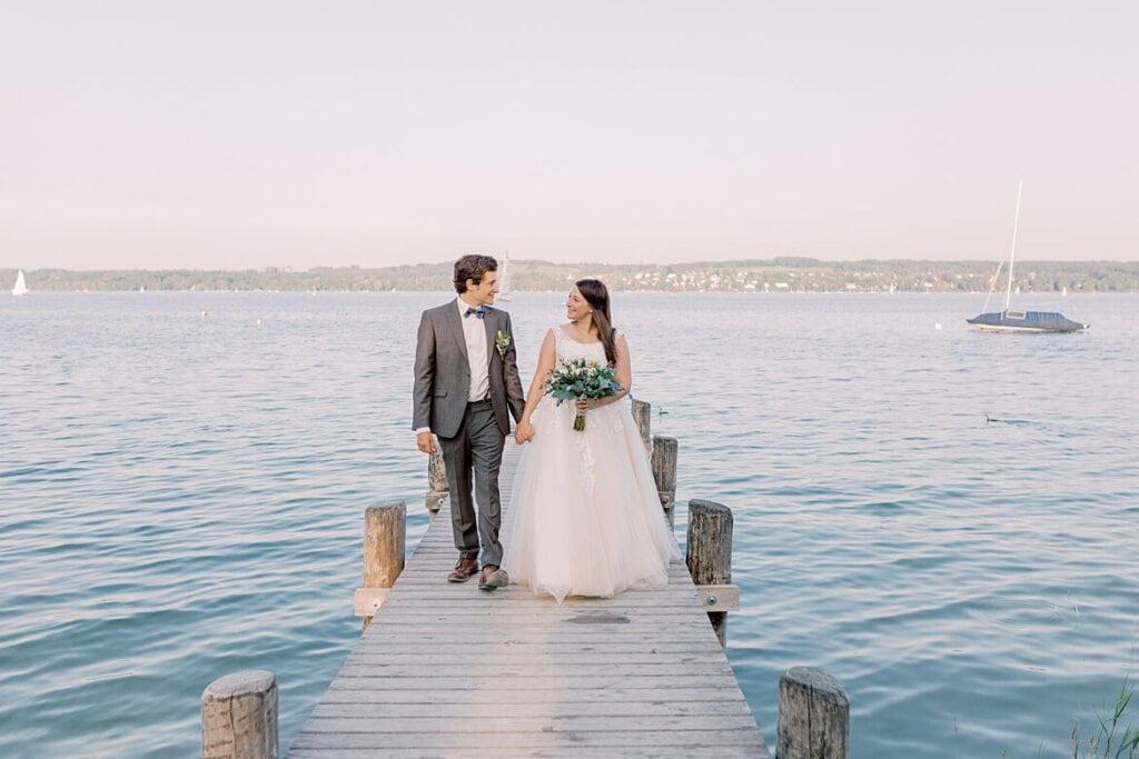 Brautpaar läuft auf Steg am Ammersee