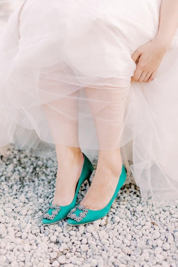 Braut rafft Brautkleid und Manolo Blahnik Schuhe in Smaragd gucken hervor