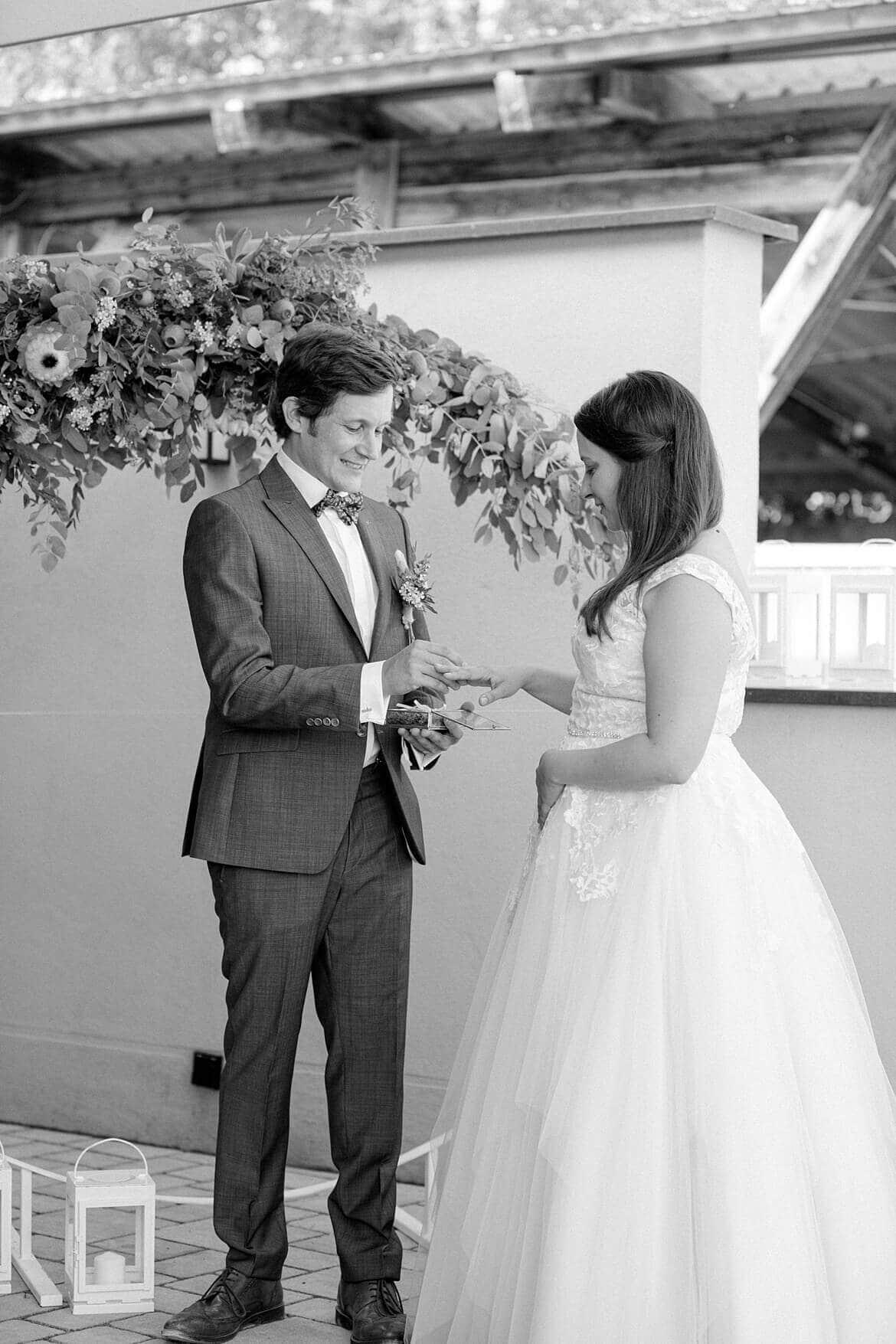 Schwarz Weiß Foto wie sich Brautpaar Ringe ansteckt