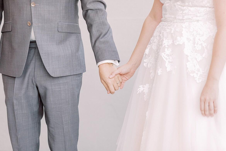 Brautpaar fasst sich an den Händen