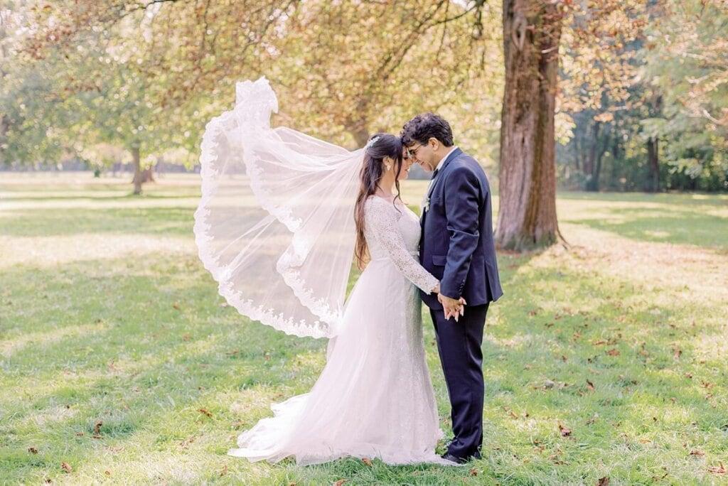 Brautpaar mit wehendem Schleier im Park