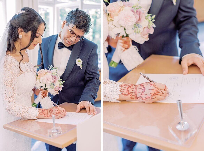 Brautpaar unterzeichnet Eheurkunde im Standesamt Mandlstraße in München