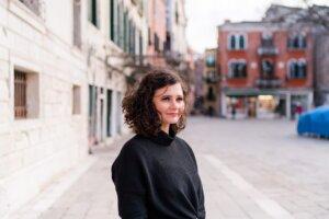 Frau mit Locken in Venedig auf einem Platz. Die Haare wehen im Wind.