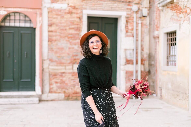 Frau in Venedig, lacht und hält einen Blumenstrauß in der Hand