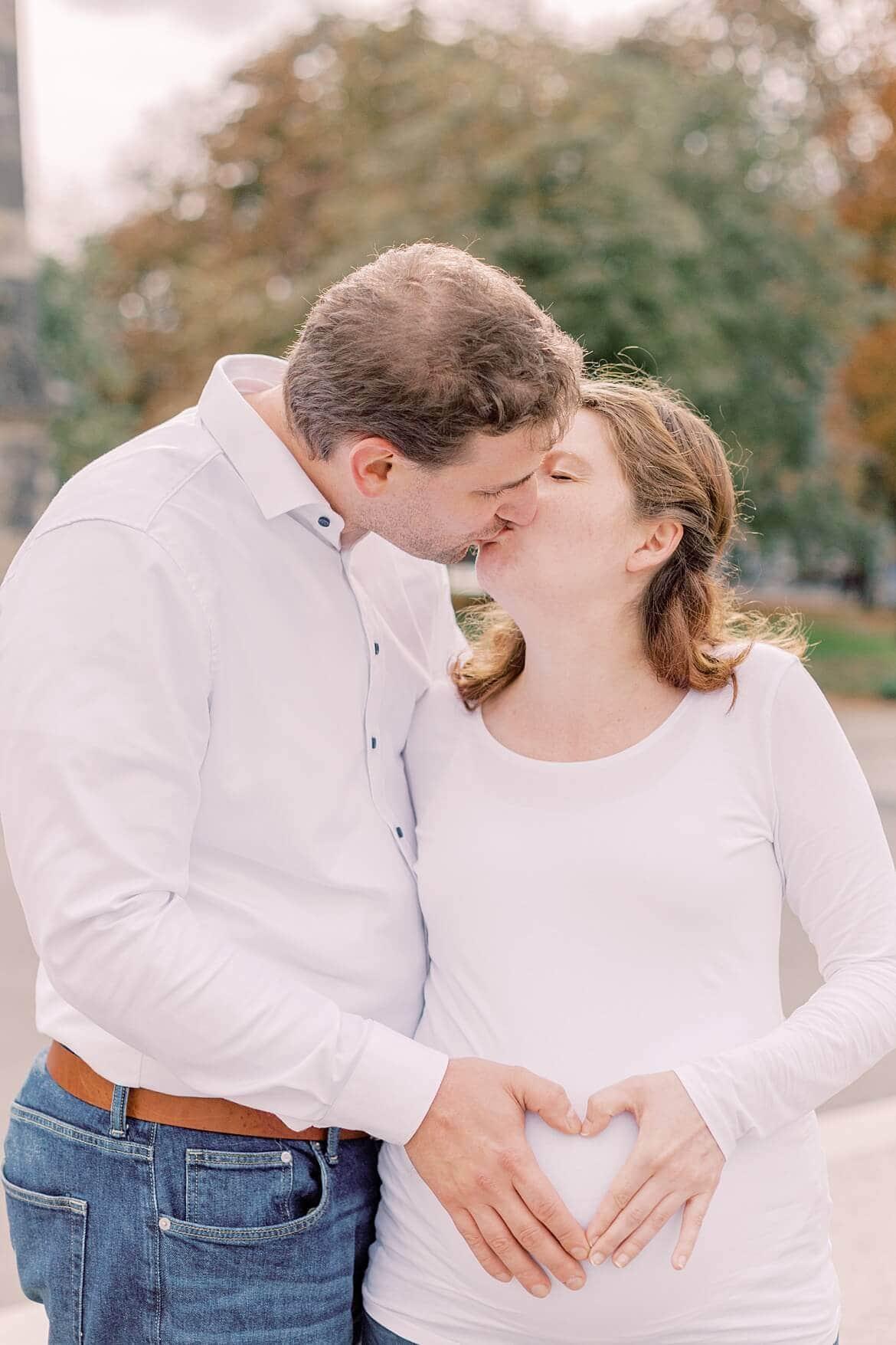 Paar küsst sich und formt ein Herz auf Babybauch
