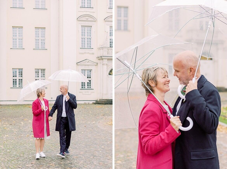 Brautpaar unter einem Regenschirm vor dem Schloss Köpenick Berlin