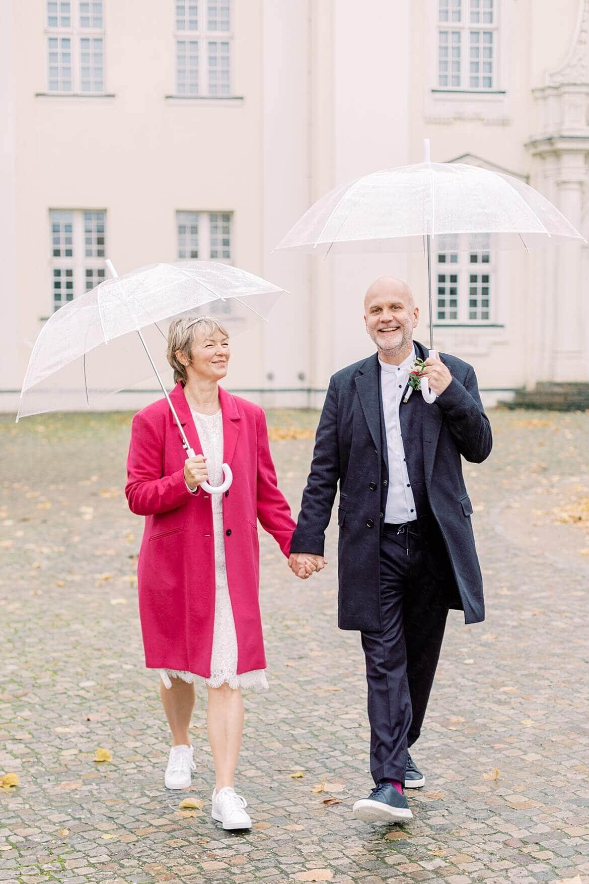 Brautpaar läuft unter Regenschirmen im Herbst vor dem Schloss Köpenick Berlin
