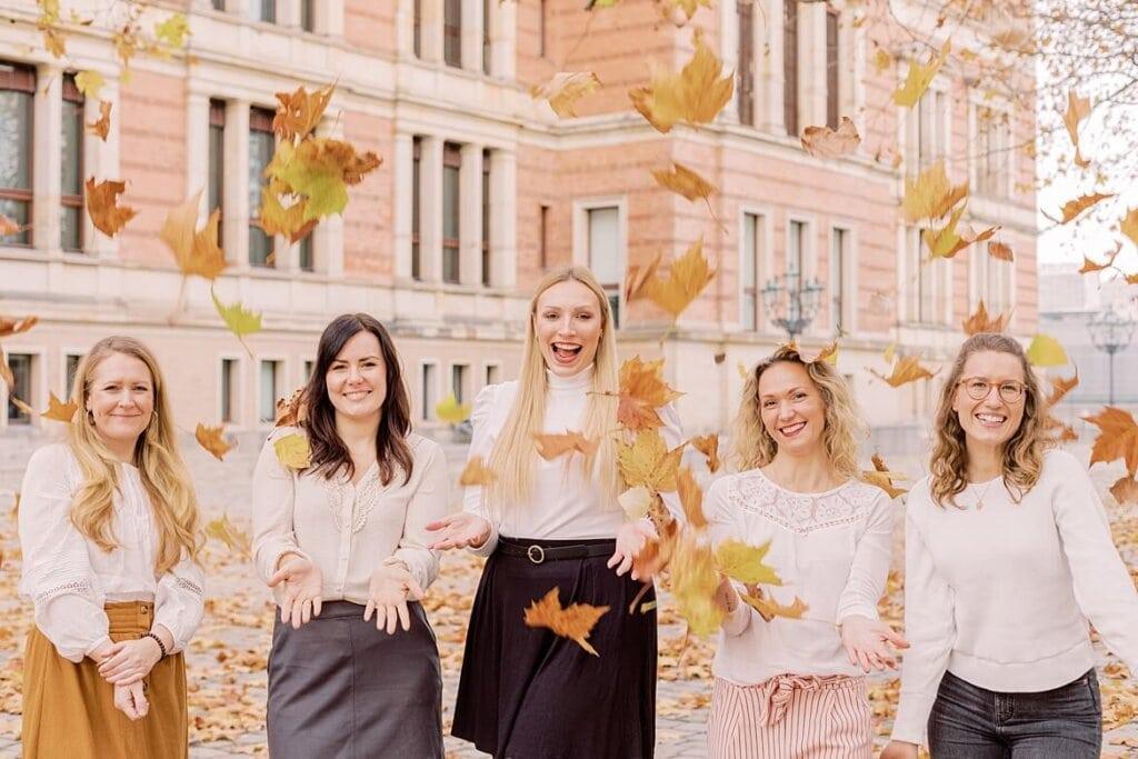 Frauen werfen Herbstblätter in die Luft