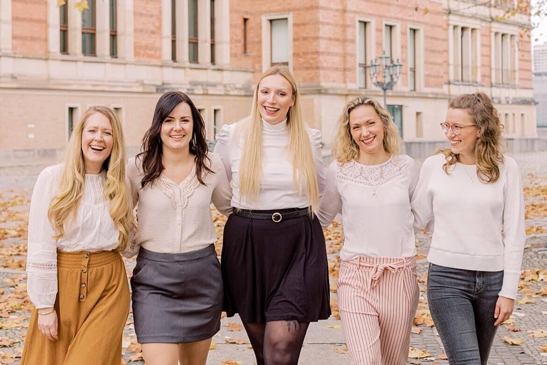 Fünf Frauen umarmen sich und lachen