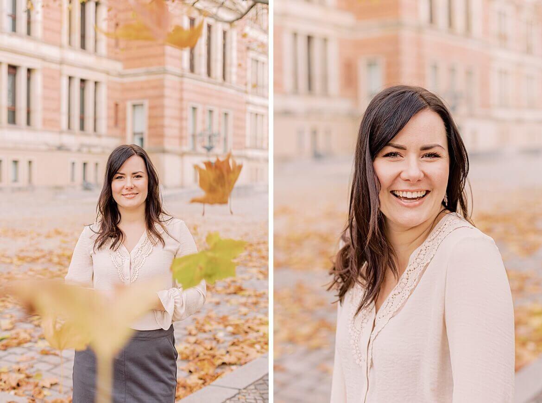Frau steht im Blätterregen und lacht