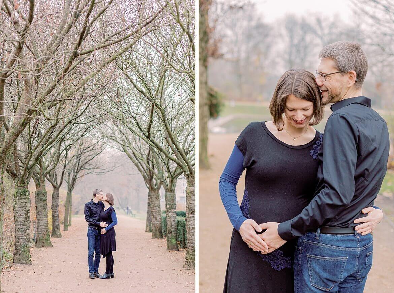 Schwangeres Paar küsst sich im Park unter Bäumen