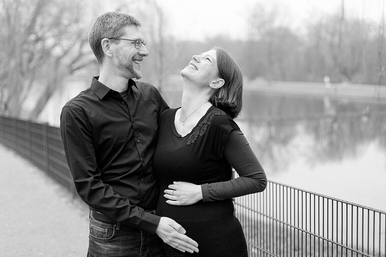 Schwangeres Paar lacht herzlich