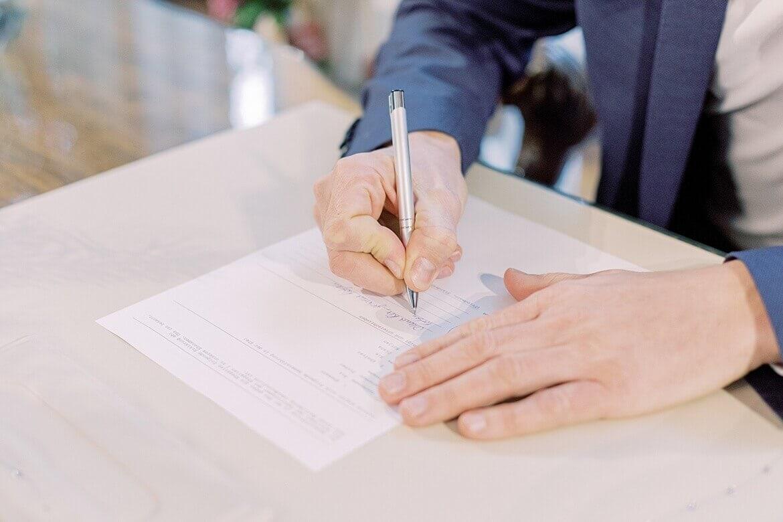 Bräutigam unterschreibt Eheurkunde