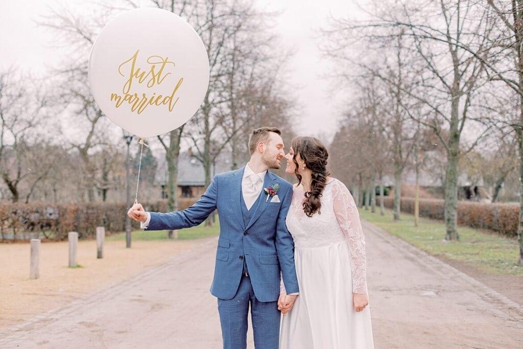Brautpaar mit Ballon küsst sich