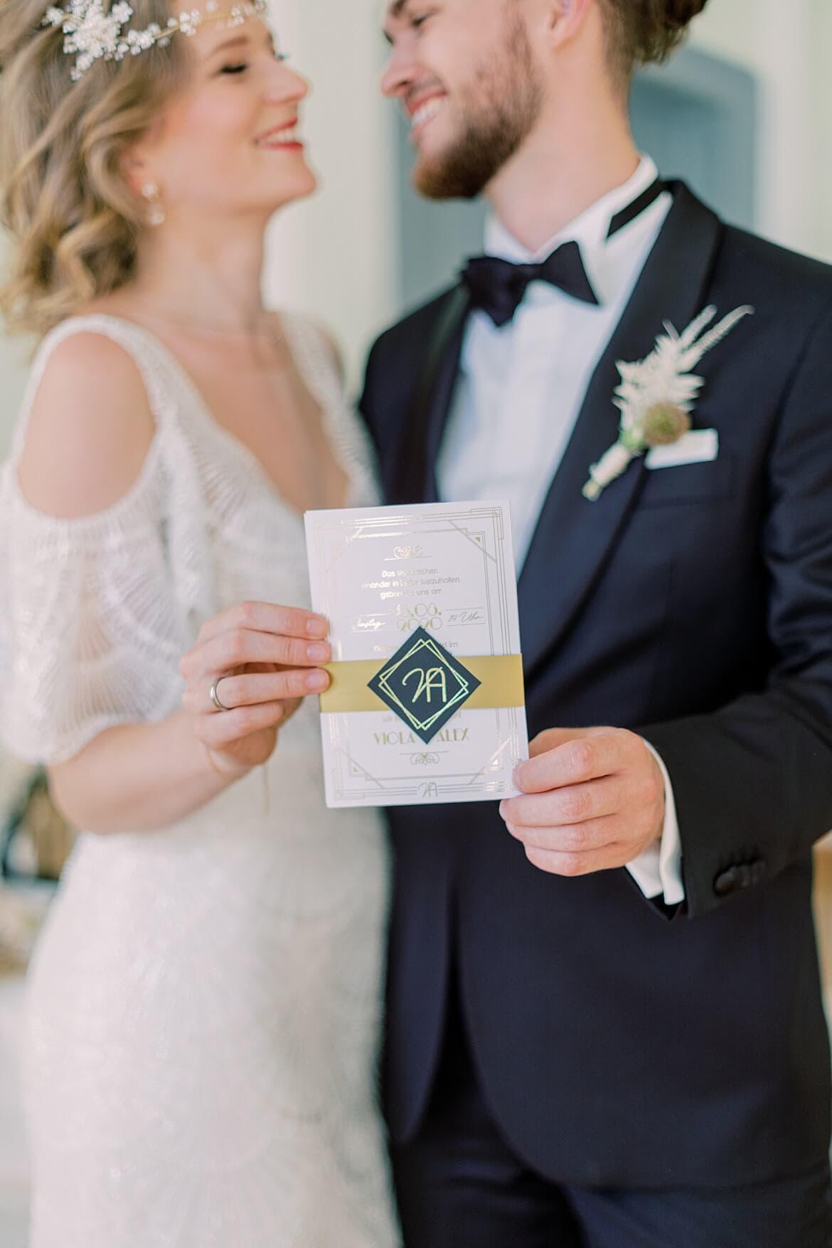 Brautpaar hält Einladung in der Hand