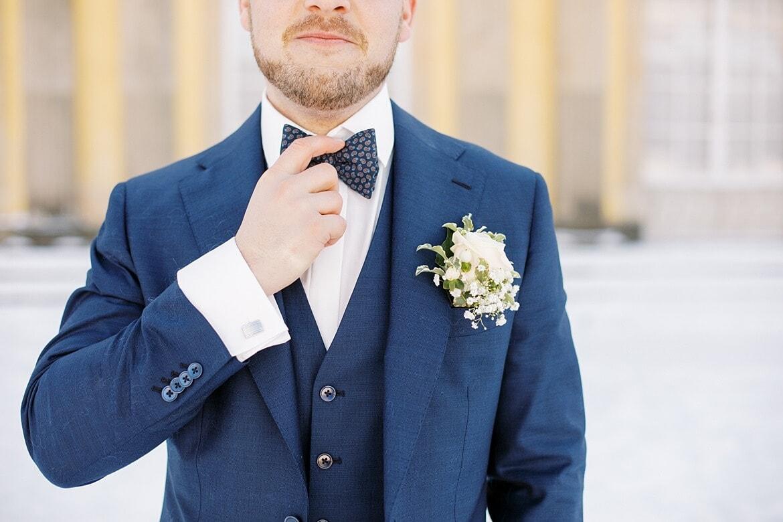 Bräutigam fasst sich an Fliege