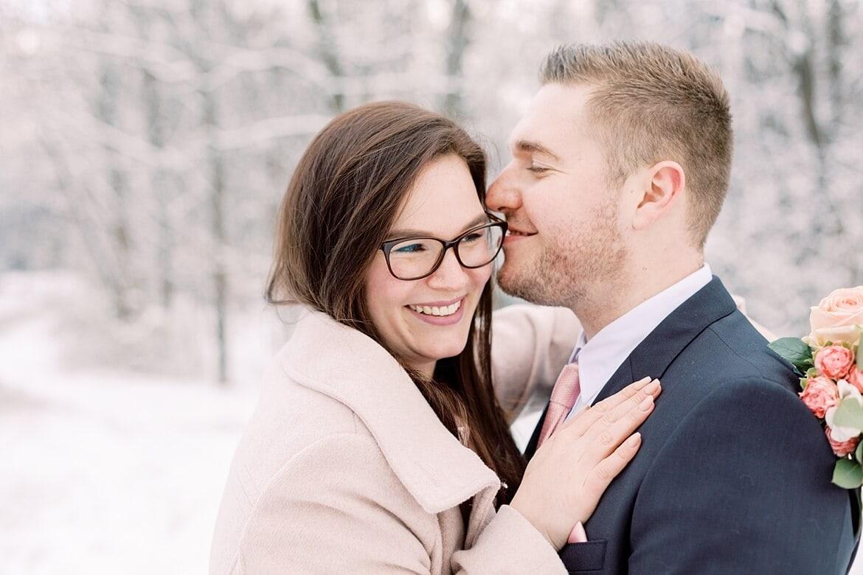 Paar kuschelt sich aneinander im Schnee