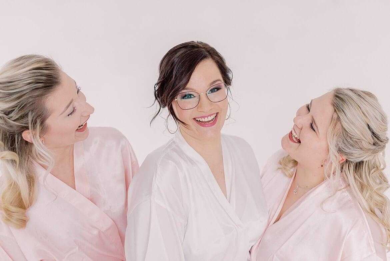 Braut und ihre Trauzeuginnen lachen in Roben