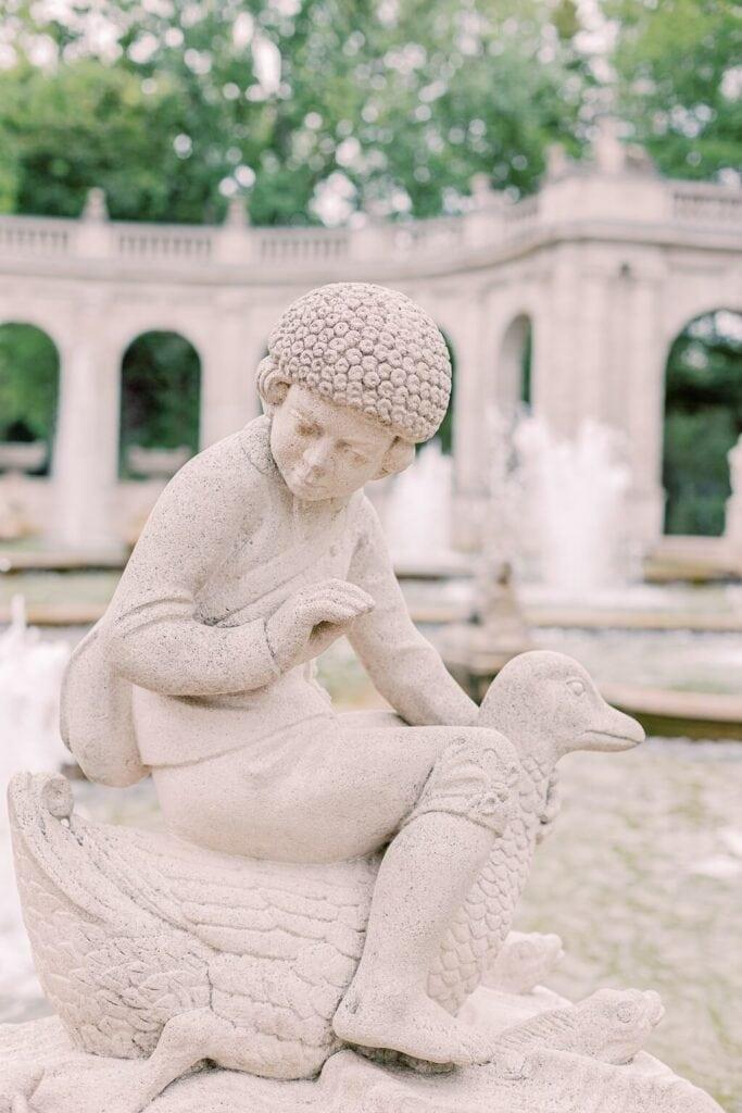 Eine Steinfigur: Ein Junge reitet auf einer Gans. Im Hintergrund ein Springbrunnen.