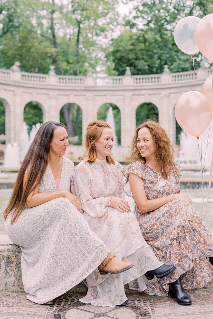 Drei Frauen sitzen am Rand eines Springbrunnens und schauen sich lächelnd an. Eine Frau hat Luftballons in der Hand. Alle Frauen tragen lange pastellfarbene Kleider.