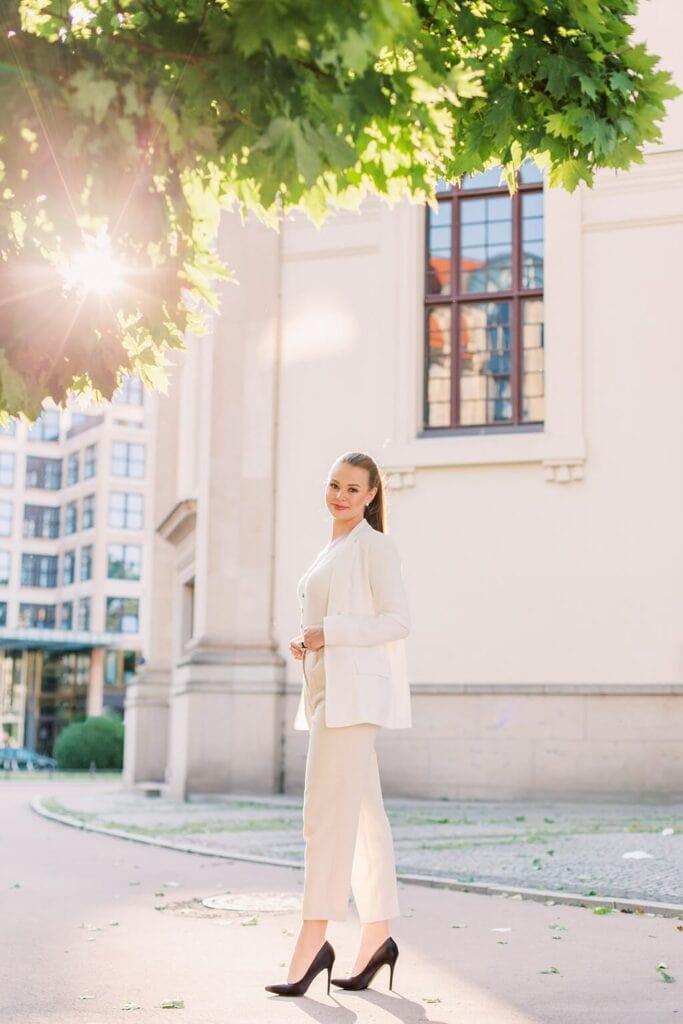 Frau im weißen Hosenanzug steht vor einem alten Gebäude und schaut in die Kamera. Ihre Haare sind zu einem Zopf gebunden. Links steht ein Baum mit grünen Blättern durch den die Sonne scheint. Berlin, Gendarmenmarkt.