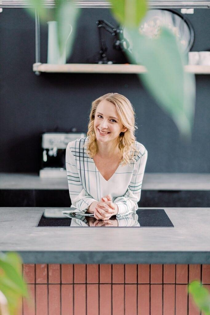 Eine Frau stützt sich auf eine Herdplatte und schaut lachend in die Kamera.