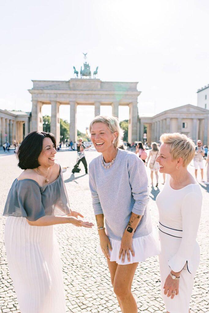 Drei Frauen stehen vor dem Brandenburger Tor in Berlin. Sie sind Weiß und Grau gekleidet. Sie lachen sich gegenseitig an.