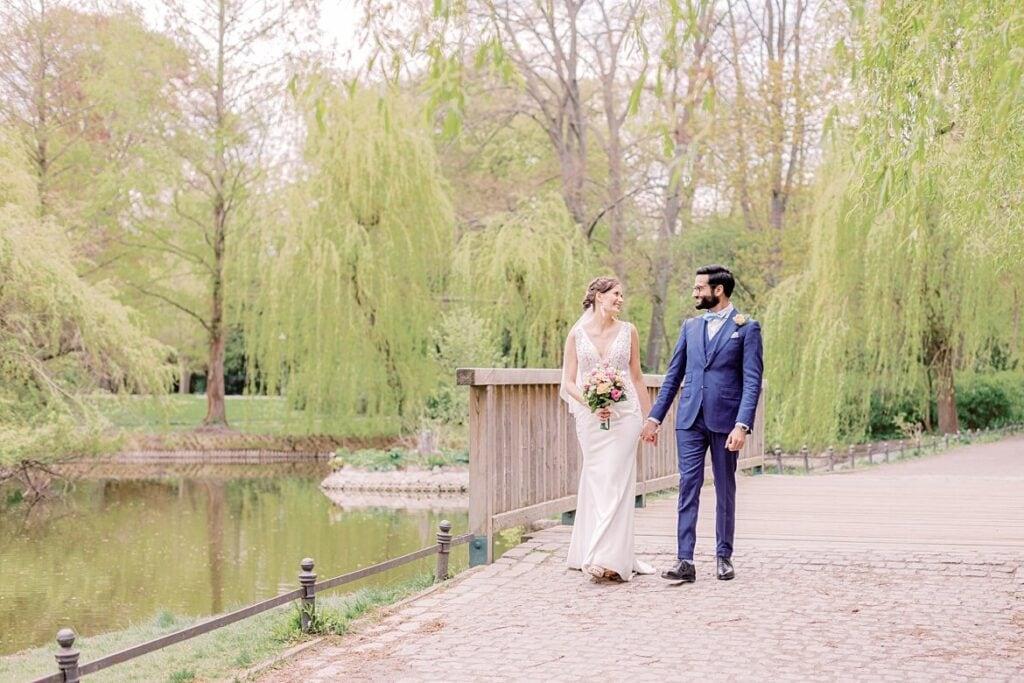 Brautpaar spaziert über Brücke an einem Teich im Stadtpark Steglitz