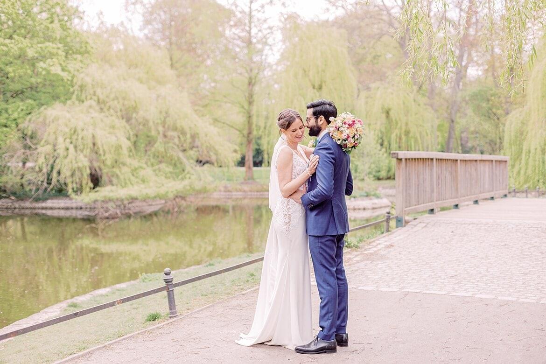 Brautpaar umarmt sich vor einem Teich im Stadtpark Steglitz