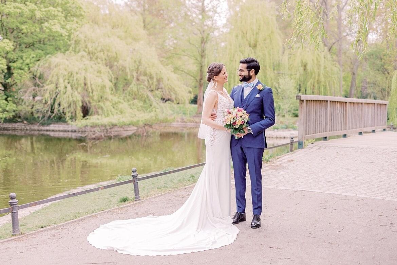 Brautpaar steht am Teich und schaut sich an im Stadtpark Steglitz