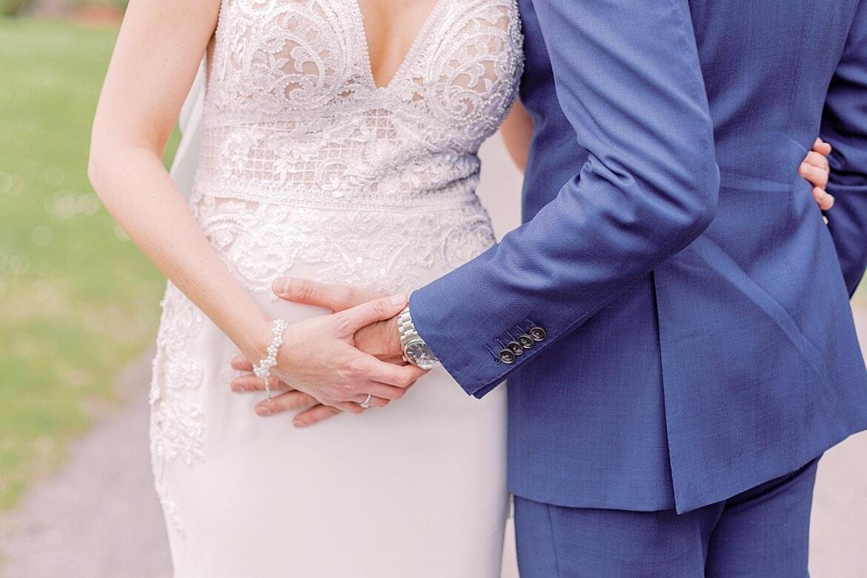 Nahaufnahme wie Bräutigam den Bauch der Braut hält