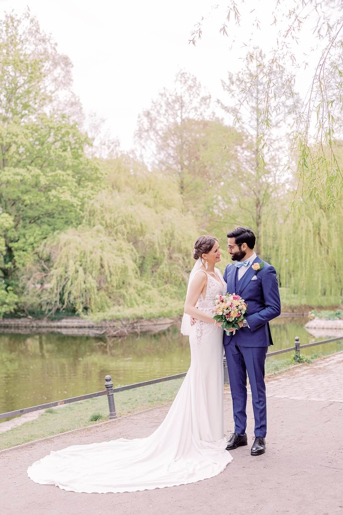 Brautpaar im Stadtpark Steglitz - Braut ist eingedreht, sodass man die Schleppe des Brautkleids sieht