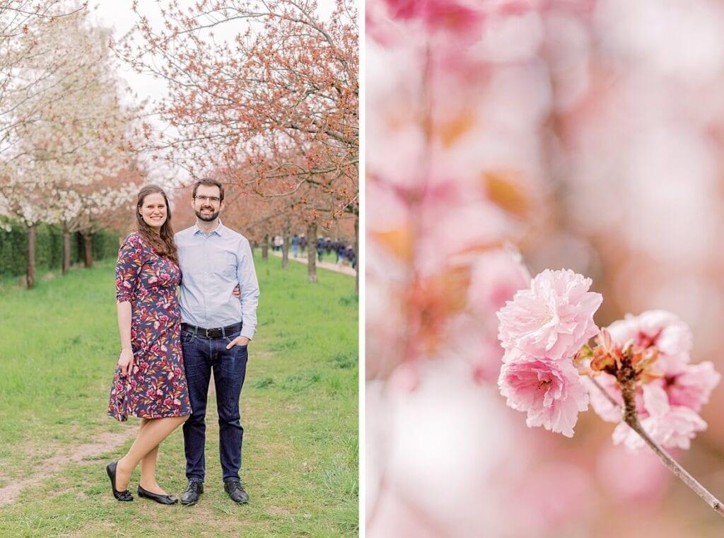 Paar steht am Mauerweg unter Kirschblüten