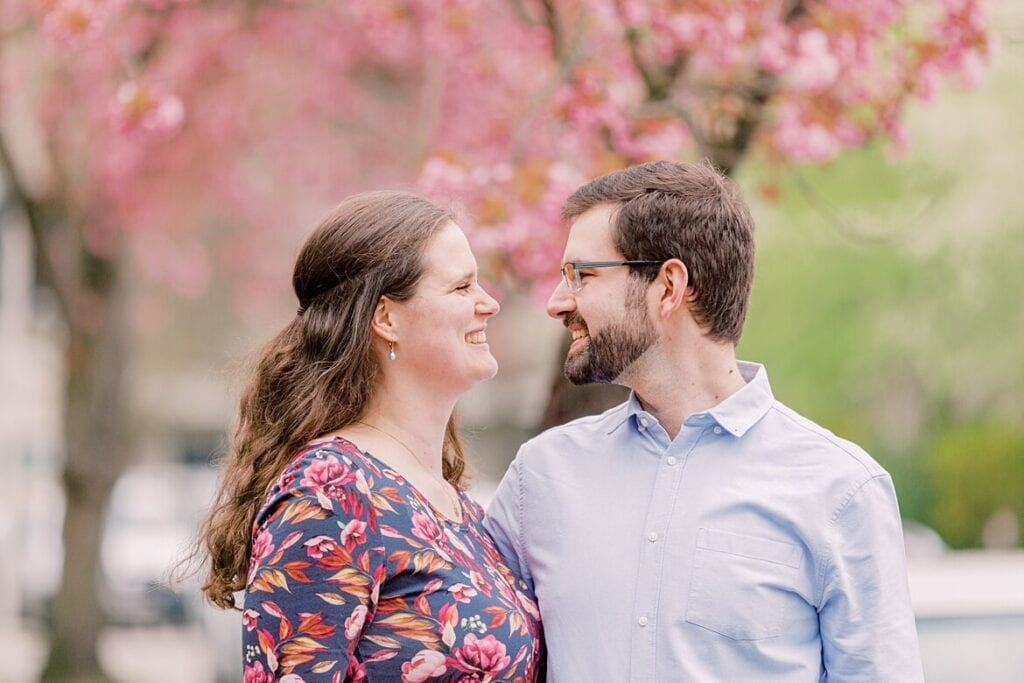 Paar schaut sich lachend an. Im Hintergrund sind Kirschblüten