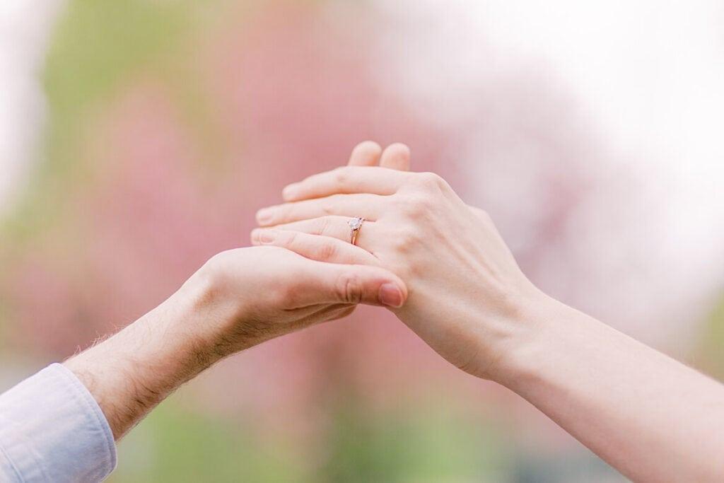 Nahaufnahme von Händen, die sich halten. Die Frau hat einen Verlobungsring.