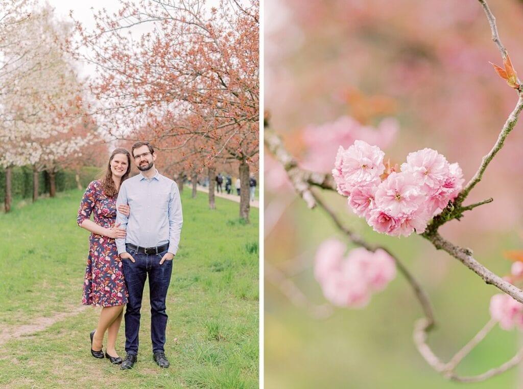 Paar steht lachend unter Kirschblüten