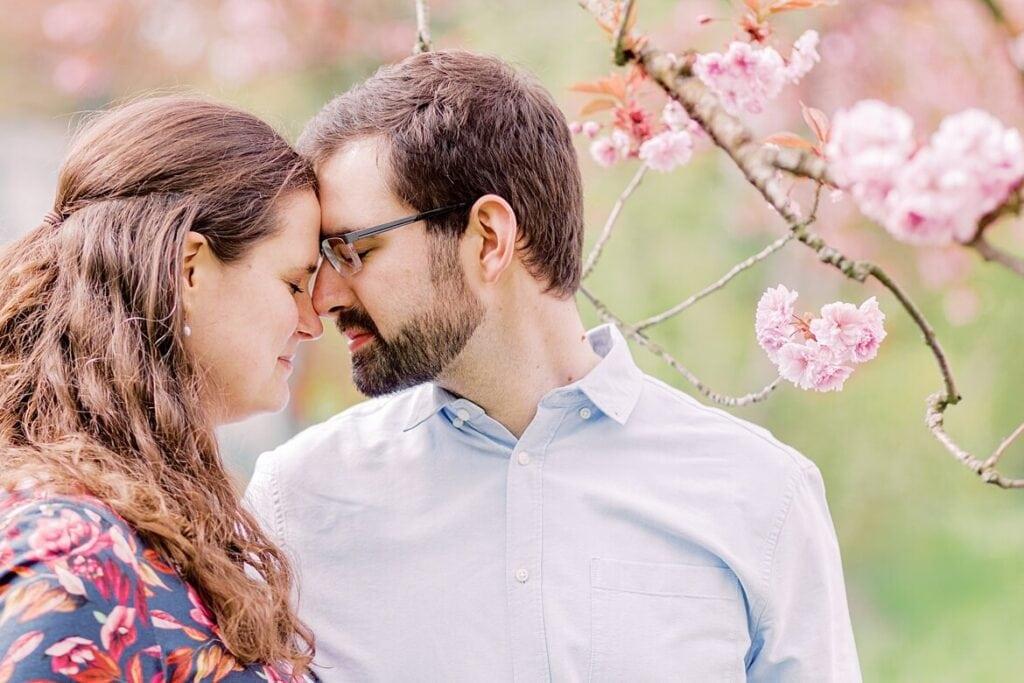Paar hat Stirn an Stirn gelegt. Ist umrahmt von Kirschblüten