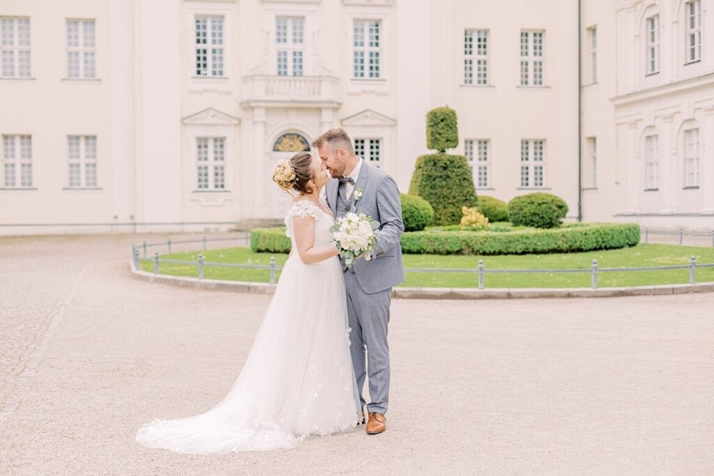 Brautpaar küsst sich vor dem Schloss Köpenick