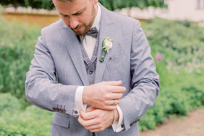 Bräutigam schaut auf seine Manschettenknöpfe