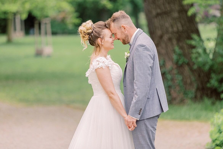 Brautpaar schmiegt sich im Park vom Schloss Köpenick aneinander