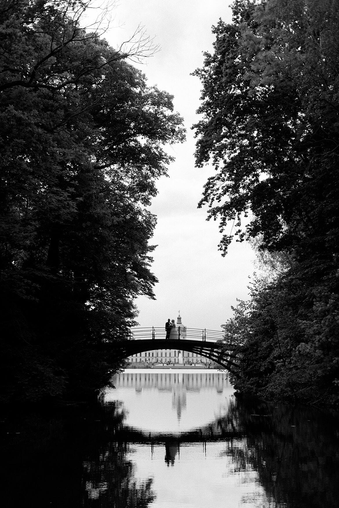 Schwarz Weiß Foto eines Brautpaares auf einer Brücke, im Hintergrund das Schloss Charlottenburg Berlin