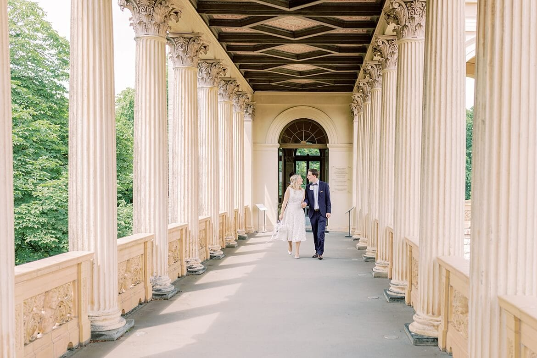 Brautpaar läuft im Säulengang Belvedere Pfingstberg