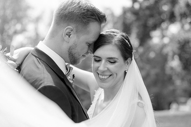 Schwarz Weiß Foto des Brautpaares, Schleier fliegt im Vordergrund